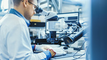 Electronics Factory Worker In White Work Coat Is Soldering A Printed Circuit Board Through A Digital Microscope. High Tech Factory Facility.