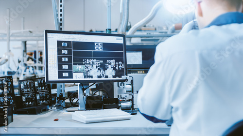Fotografie, Tablou  Electronics Factory Worker in White Work Coat Inspects a Printed Circuit Board on a Computer Screen that is connected to a Digital Microscope