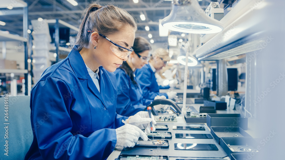 Fototapeta Woman Electronics Factory Worker in Blue Work Coat and Protective Glasses is Assembling Smartphones with Screwdriver. High Tech Factory Facility with more Employees in the Background.