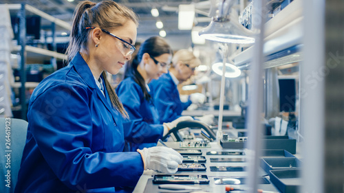 Female Electronics Factory Workers in Blue Work Coat and Protective Glasses Assembling Printed Circuit Boards for Smartphones with Tweezers Fototapete