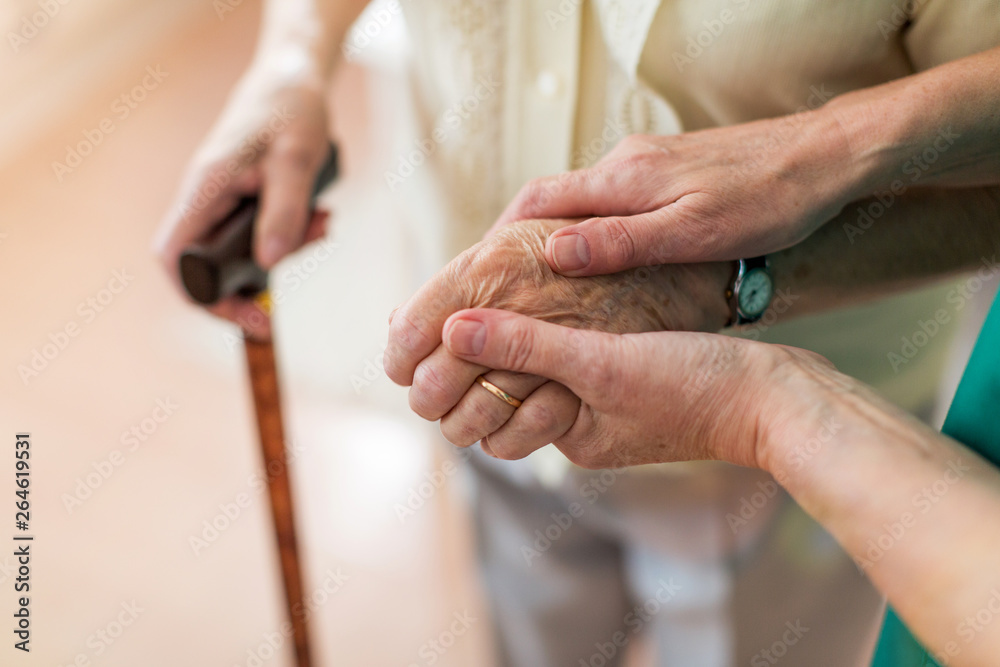 Fototapety, obrazy: Nurse consoling her elderly patient by holding her hands