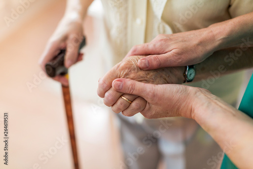Obraz Nurse consoling her elderly patient by holding her hands - fototapety do salonu