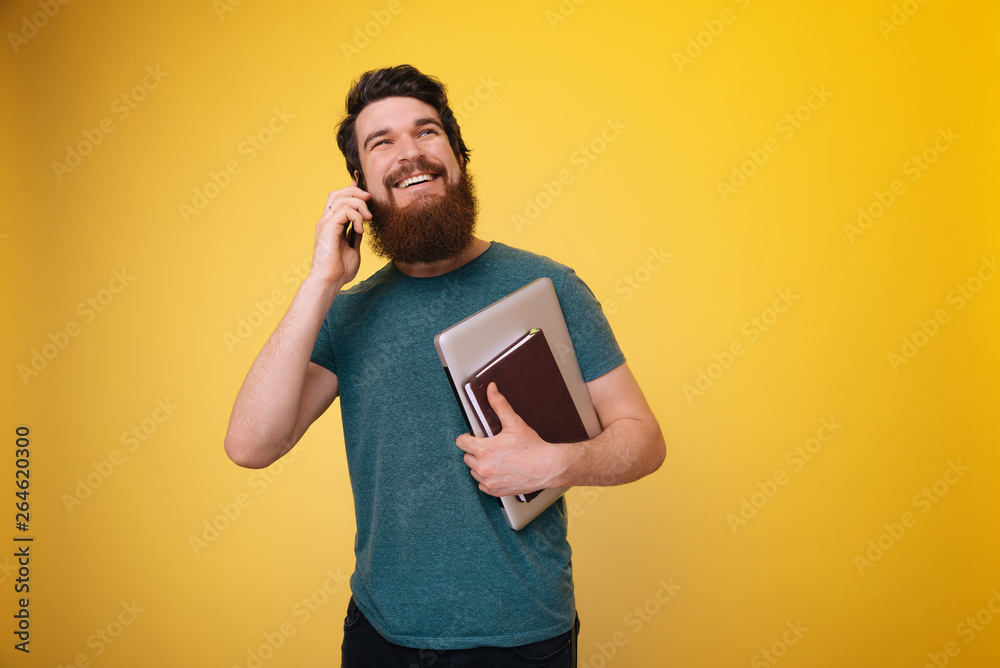 Fototapeta A handsome worker man, with beard, is talking on phone and holding laptop, notebook