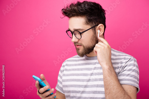 Hnadsome aman wearing glasses, using airpods, over isolated pink packground Canvas Print