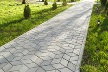 The Footpath In The Park Is Paved With Diamond Shaped Concrete Tiles. On The Lawn - Small Decorative Lights.
