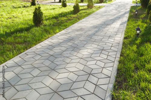 The footpath in the park is paved with diamond shaped concrete tiles Fotobehang