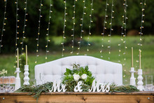 Wedding Sweetheart Table With Mr And Mrs Sign, Flowers And A White Couch