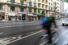 A Man On A Bycycle Rushing Through A Street In Budapest
