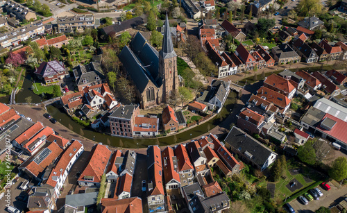 Fototapeta Aerial historic dutch village Maasland with central church and canal curving around obraz na płótnie
