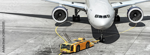 Photo sur Aluminium Avion à Moteur airplane on airport runway with pushback tractor attached to plane nose gear aerial top front view passenger jet engine aircraft towing by ground vehicle to terminal gate black and white wide banner