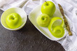 green apples on the table. green one-piece and peeled the apples in the white plate closeup. background with apples.