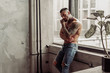 Fashion portrait of Sexy naked male model with tattoo and a black beard standing in hot pose on near the window. Loft room interior with grey concrete wall. Professional Studio image