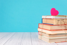 Stack Of Books And Pink Heart. Books With Jute Ribbon Bow As Gift On Blue Background. Education Background With Copy Space, Back To School Concept