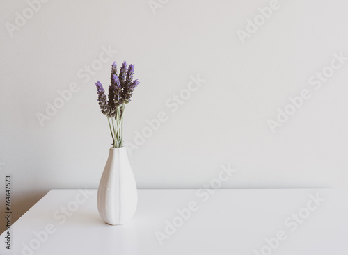 Foto op Aluminium Lavendel Close up of lavender sprigs in small white vase on side table against neutral wall background (selective focus)
