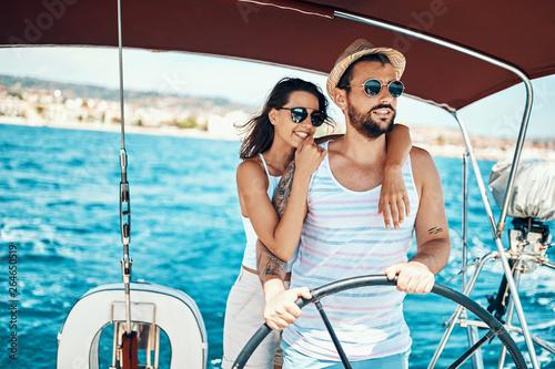 Fotografia  Romantic couple on a yacht enjoy bright sunny day on vacation.