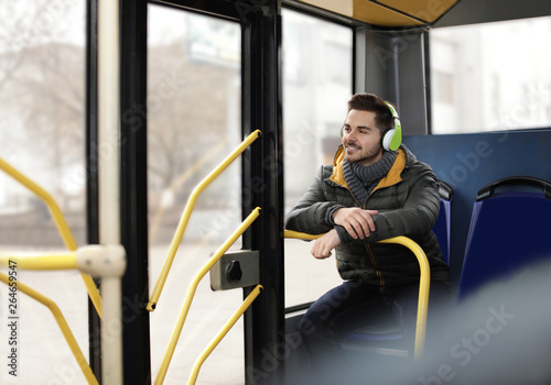 Foto  Young man listening to music with headphones in public transport