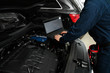 Technician checking car with laptop at automobile repair shop, closeup