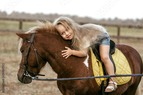 Photo Adorable little girl riding a pony at summer