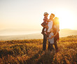 Leinwandbild Motiv Happy family: mother, father, children son and daughter on sunset.