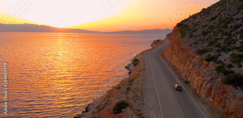 Fotografía DRONE: Flying behind tourist car driving down empty road leading around island