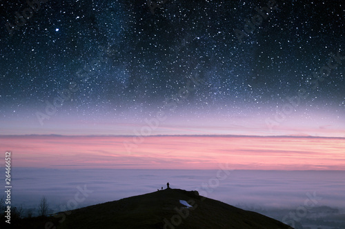 Fotografie, Obraz  A concept edit of a man with his dogs standing on the edge of a mountain, looking out across a misty morning with stars in the night sky