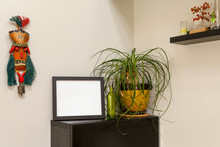 Blank Black Horizontal Picture Frame On A Shelf With A Ponytail Palm  And A Tribal Mask. For Mocking Up Photos And Artwork.
