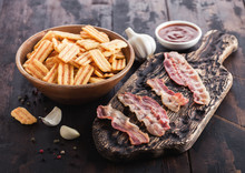 Bacon Flavoured Snacks Chips With Grilled Bacon Rashers On Vintage Chopping Board With Garlic And Sauce On Wooden Background.