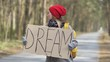 Young hitchhiking woman go on road with poster dream. Back view