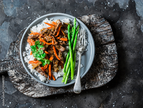 Valokuva  Asian style lunch - spicy fried beef, rice, asparagus on dark background, top vi