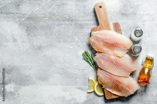Fish fillet on a cutting Board with lemon slices, spices and oil in a bottle Fototapeta