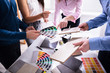 Businesspeople Choosing Color From Color Swatches