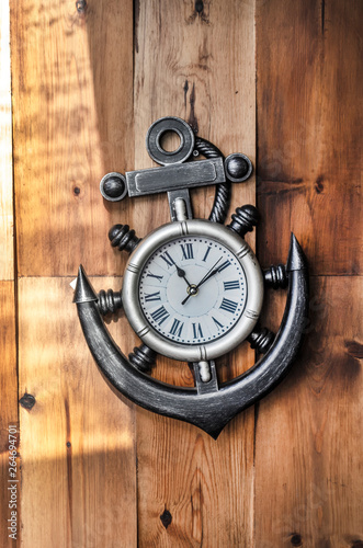Photo A nautical metal clock in the shape of an anchor on a wooden background showing the time