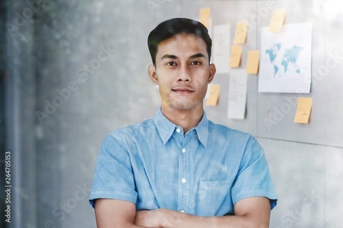 Fototapety, obrazy: Portrait of Happy Young Asian Businessman standing by the Window Crossed Arms and Smiling in Office. Document's Data Plans and Project as background. Snap from Outside Building