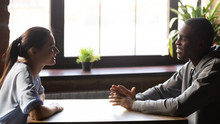 Diverse Millennial Positive Couple Sitting At Table Chatting Feels Good