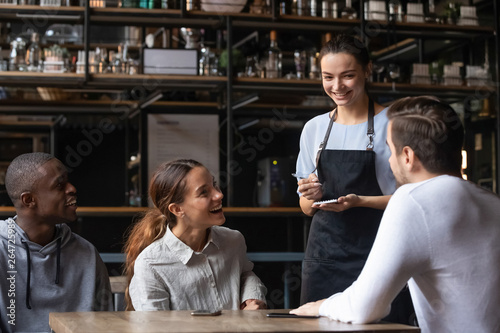 Diverse friends sitting in restaurant placing order talking with waitress Canvas Print