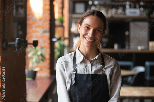 Cuadros en Lienzo Happy mixed race female in apron smiling looking at camera
