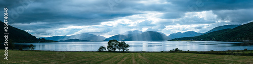Obraz na plátně Mystic landscape lake scenery in Scotland: Cloudy sky, meadow, trees and lake with sunbeams, mountain range in the background