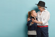 Leinwandbild Motiv Funny positive old woman embraces small granddaughter, makes photo on modern cell phone, have fun taking selfie, look at each other, use technologies. Family, lifestyle and relations concept