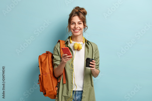 Photo Studio shot of glad female student has coffee break after lectures, listens audio book in headphones, enjoys record from website, uses mobile phone for chatting online, has rucksack on back
