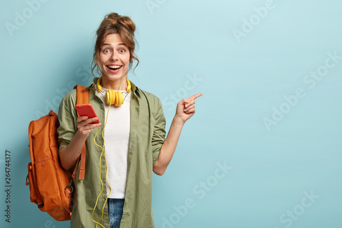 Foto  Studio shot of happy teenage girl holds mobile phone, checks email, gets new not