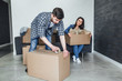 Happy young couple packing cardboard boxes during relocation!