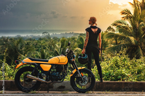 girl at sunset near the motorbike