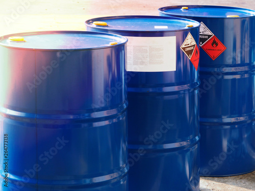 Fototapeta the close-up shot of blue color hazardous dangerous chemical drum barrels ,have warning labels of corrosive & flammable liquid in daylight on daytime. obraz