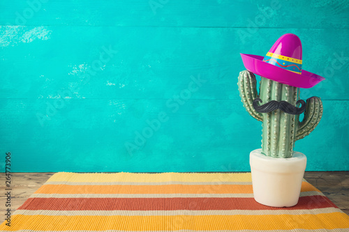 Poster Cactus Cinco de Mayo holiday background with Mexican cactus and party sombrero hat on wooden table