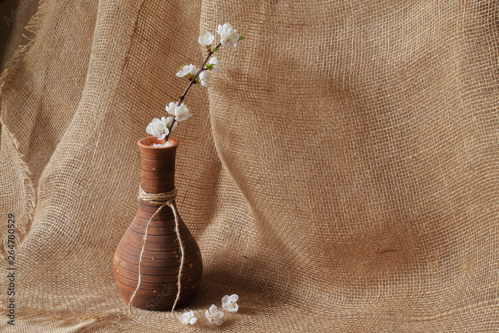 Fototapety, obrazy: Branch of apple tree with white beautiful flowers in original clay vase on rough homespun jute background. Concept is style, elegance and beauty.