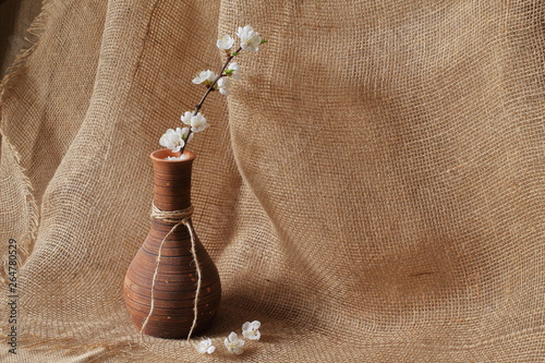 Fototapeta Branch of apple tree with white beautiful flowers in original clay vase on rough homespun jute background. Concept is style, elegance and beauty. obraz