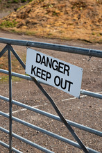 Danger Keep Out Sign On Metal Gate Boundary To Disused Contaminated Factory Site
