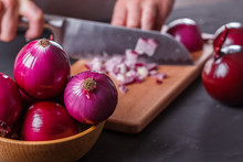 Young Woman In A Gray Aprons Cuts Red Onion