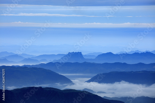 Abstract Image, Mountain Silhouettes at dawn - rolling jagged mountain peaks, cold blue color hues. Panoramic Abstract Background Image, overcast skies, layers of rolling mountains in the distance.