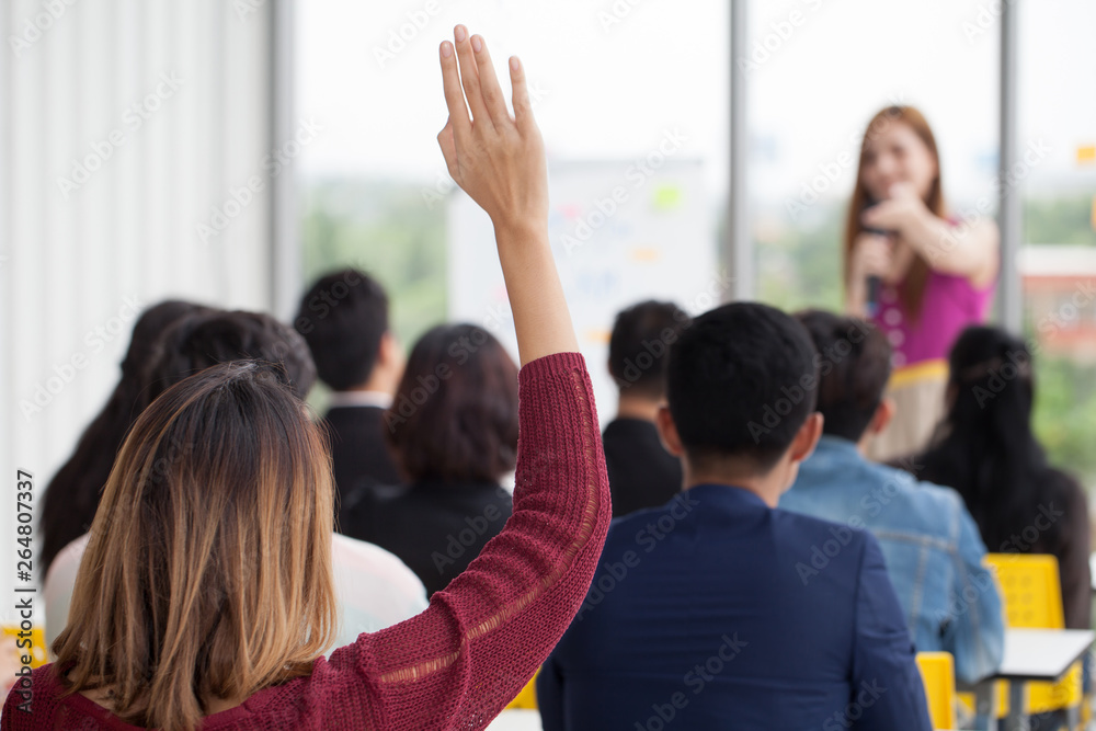 Fototapeta young businesswoman raising hand  to question from Speaker in Seminar. Group Meeting . Conference  Concept . Rear back view